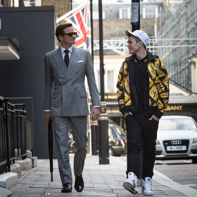 Eggsy and Harry from Kingsman walk down the street together, in their respective attire.