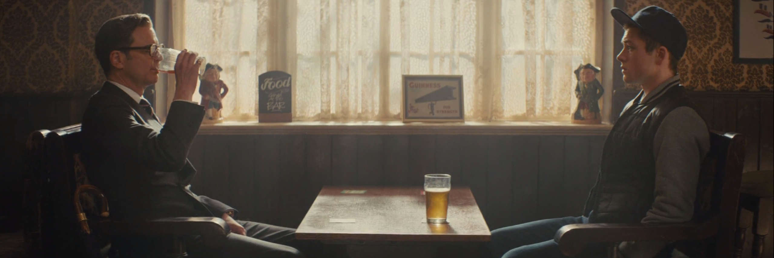 Eggsy and Harry from Kingsman sit in a pub, drinking beer.