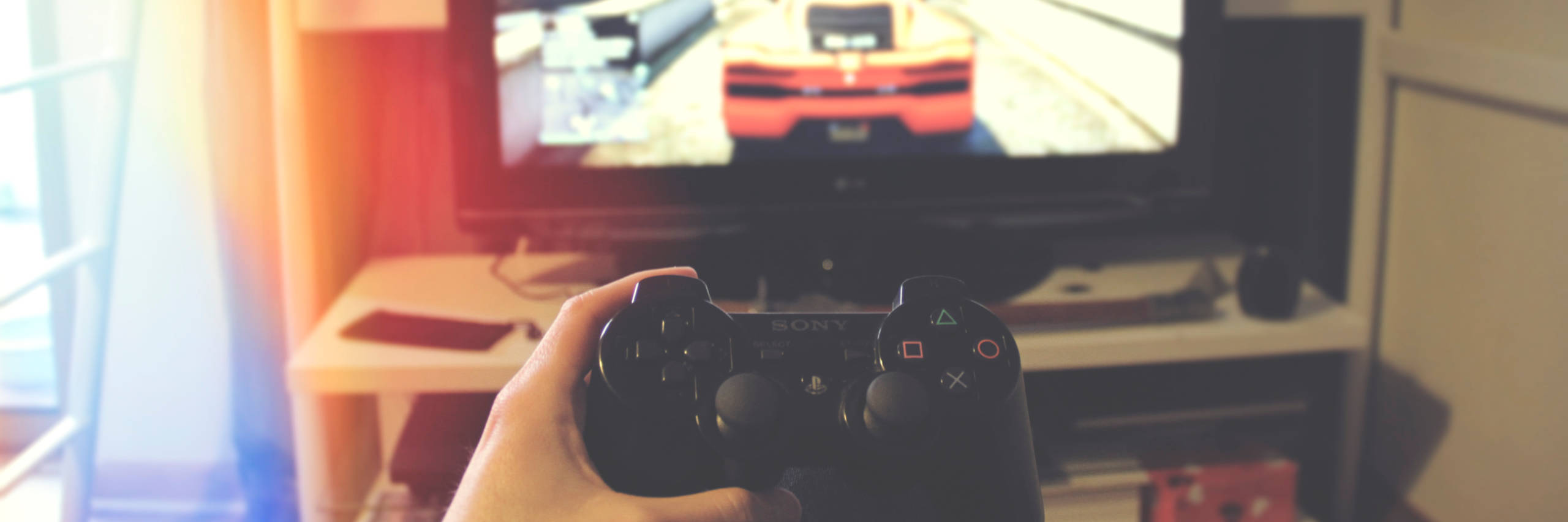 Hand holding a PS2 controller, with TV in the background.