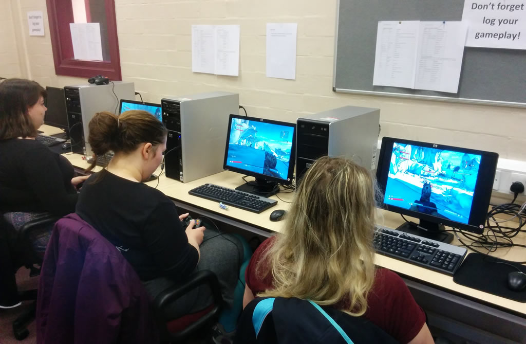 3 students sit at computers in a lab, playing video games.