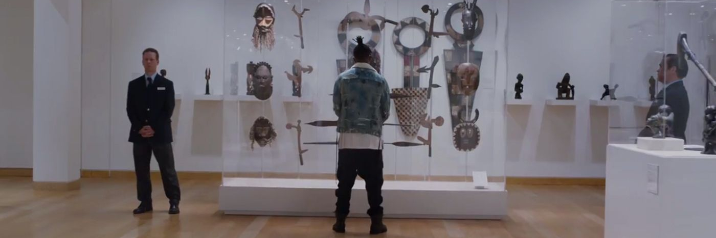 Killmonger in front of a case of artefacts at a museum
